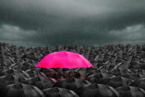 parapluie rose au milieu de parapuie noir